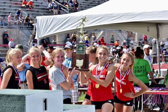 The Indian Hill girls track and field team lift up their 2019 team state championship.
