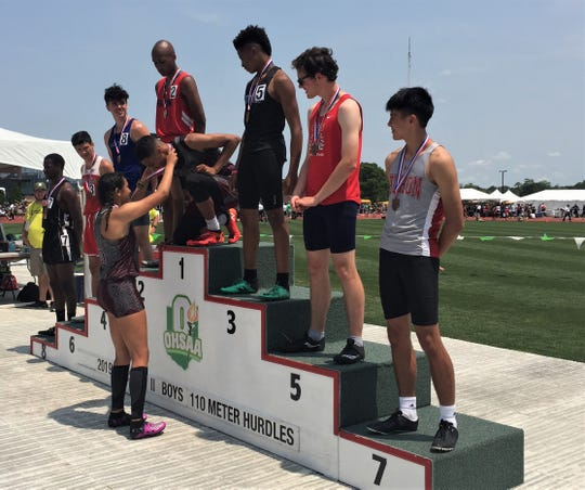 John Glenn's Hannah Clifford (standing) puts the gold medal on her brother, Joseph, who defended his state title in the 110 hurdles at Saturday's Division II state track meet. Clifford ran a time of 14.36.