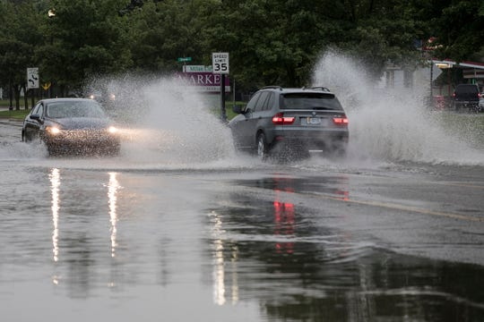 Vehicles travel through standing water on Dexter Street in Milan on Saturday, June 1, 2019.