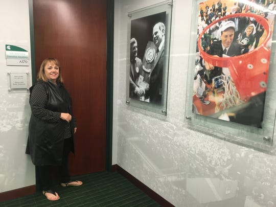 Michigan State men's basketball executive secretary Lori Soderberg stands outside her office Friday at Berkowitz Center in East Lansing, beside photos of her two bosses, Jud Heathcote and Tom Izzo.