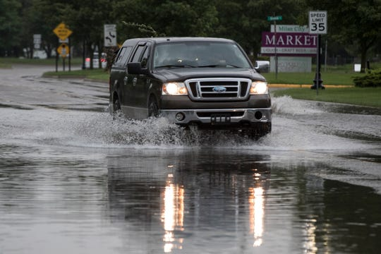Vehicles travel through standing water on Dexter Street in Milan on June 1, 2019.