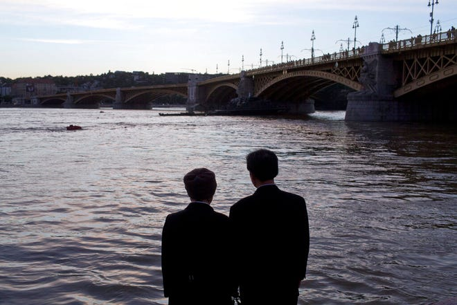 A couple stand on the banks of the Danube river next to Margit bridge where a sightseeing boat had capsized in Budapest, Hungary, Friday, May 31, 2019. As divers descended Friday into the Danube, Hungarian authorities predicted it would take an extended search to find the 21 people still missing after a boat carrying South Korean tourists was rammed by a cruise ship and sank into the river in Budapest.