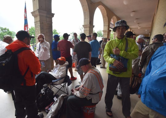 Attendees at the Detroit Grand Prix huddle at the Belle Isle Casino as rain moved in and delayed Saturday's events