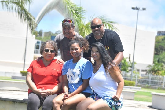 Kiani Aquiningoc Ramsey, a star softball player for North Carolina, takes a family photo on Monday May 27 at Skinner Plaza. Seated, from left are Rosita Aquiningoc, grandmother, Kiani Ramsey, Rosanne Aquiningoc Ramsey, mother. Standing from left are Francisco Aquiningoc, grandfather and Donald Ramsey, father.