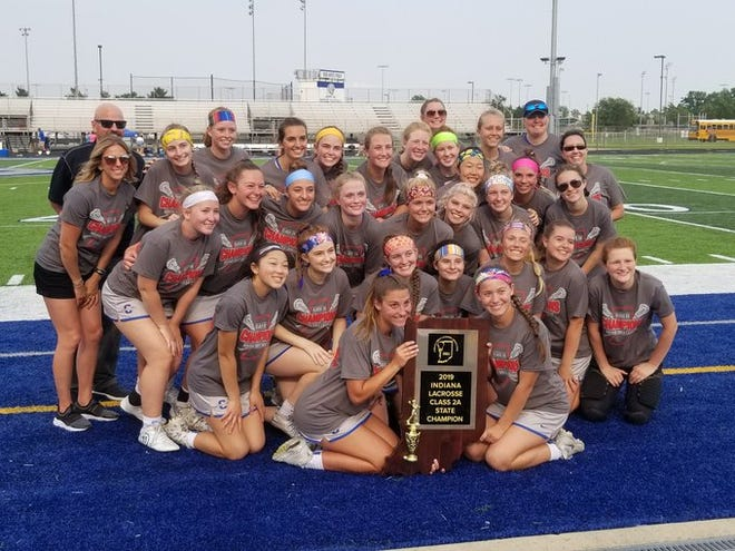 Carmel's girls lacrosse team poses with the state title trophy Saturday night.