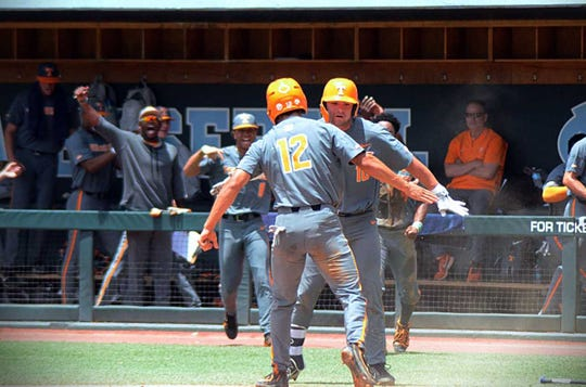 Ricky Martinez is greeted by Tennessee teammate Peter Derkay after scoring a run in an NCAA Tournament game against UNC Wilmington on Saturday, June 1, 2019.