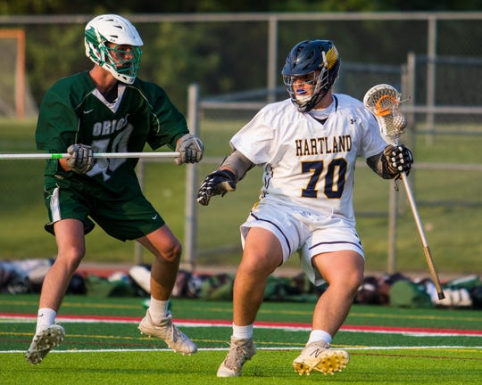 Lake Orion's Sean Henige defends Hartland's Noah Luck (70) in the state lacrosse quarterfinals at Linden on Friday, May 31, 2019.