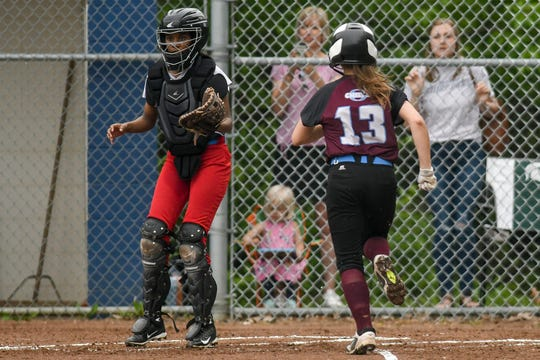 Okemos' Emily Knox, right, scores as Everett's Sue Abukar waits for the ball in the first inning on Saturday, June 01, 2019, in East Lansing.