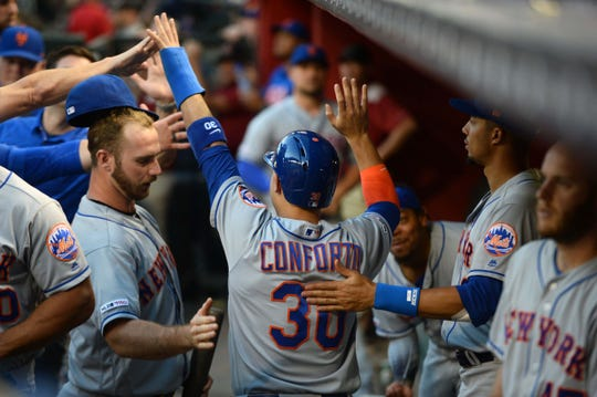 May 31, 2019; Phoenix, AZ, USA; New York Mets right fielder Michael Conforto (30) celebrates with teammates after scoring a run against the Arizona Diamondbacks during the second inning at Chase Field.