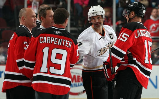 Scott Niedermayer (27) of the Anaheim Ducks shakes hands with former teammate Bobby Carpenter prior to their NHL game as former player Ken Daneyko #3 and Jamie Langenbrunner #15 of the New Jersey Devils look on at the Prudential Center on November 11, 2009 in Newark, New Jersey.