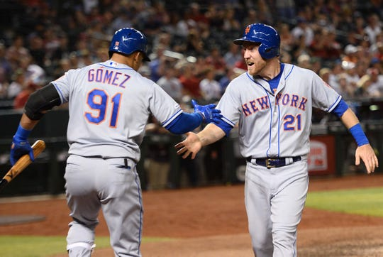 May 31, 2019; Phoenix, AZ, USA; New York Mets third baseman Todd Frazier (21) slaps hands with New York Mets right fielder Carlos Gomez (91) after scoring a run against the Arizona Diamondbacks during the eighth inning at Chase Field.