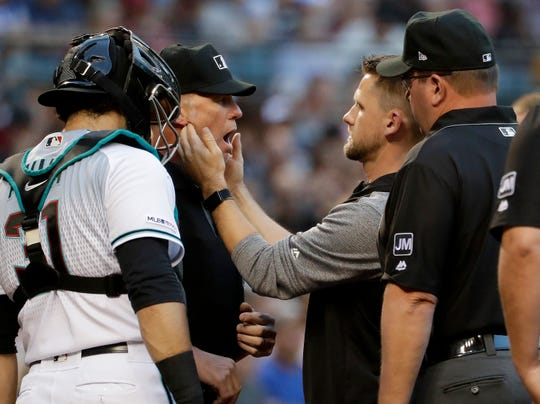 Arizona Diamondbacks catcher Alex Avila (31) watches as his trainer checks home plate umpire Jim Wolf's jaw after Wolf was hit by a foul ball off the bat of New York Mets' Todd Frazier during the second inning of a baseball game, Friday, May 31, 2019, in Phoenix.