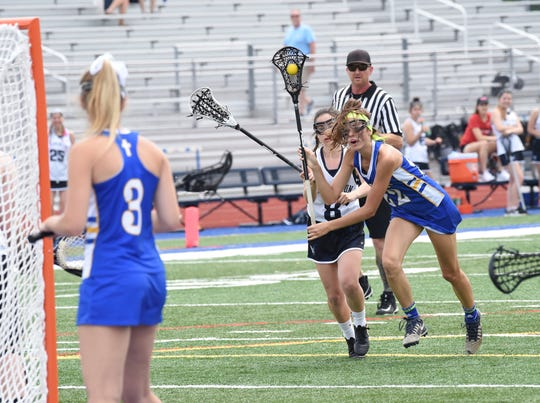 Marian's Coco Chinonis goes in for a goal against Farmington.
