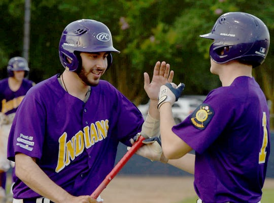 Conner Castille, left, is congratulated by St. Landry Bank Indians teammate Jobee Boone after scoring during the first inning of Thursday's game with the Opelousas General Health System Warriors.