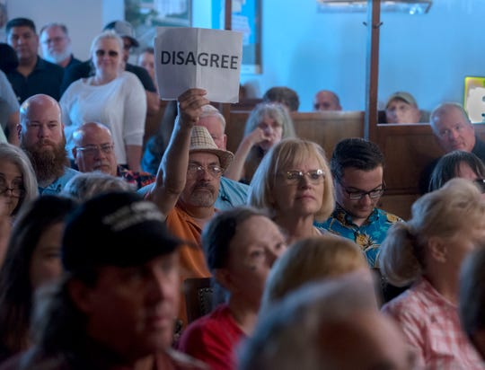 "Protesters hold up signs while Congressman Matt Gaetz speaks to the crowd Saturday, June 1, 2019, during his ""Won't Back Down"" town hall meeting at Brew Ha Ha restaurant in Pensacola."