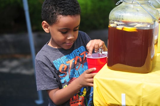 Trace Lewis, 6, prepares a cup of iced tea at his Lemonade Day stand along West Main Street.