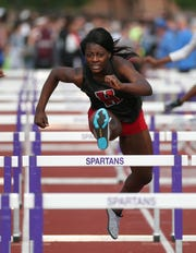 Hilton junior Anaya Dees clearing hurdles during the Division I girls 100-meter race. It was one of three first-place finishes for Dees.