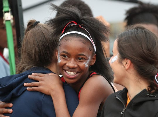 Penfield's Ay'rianna Moore celebrates after winning a 400-meter run.