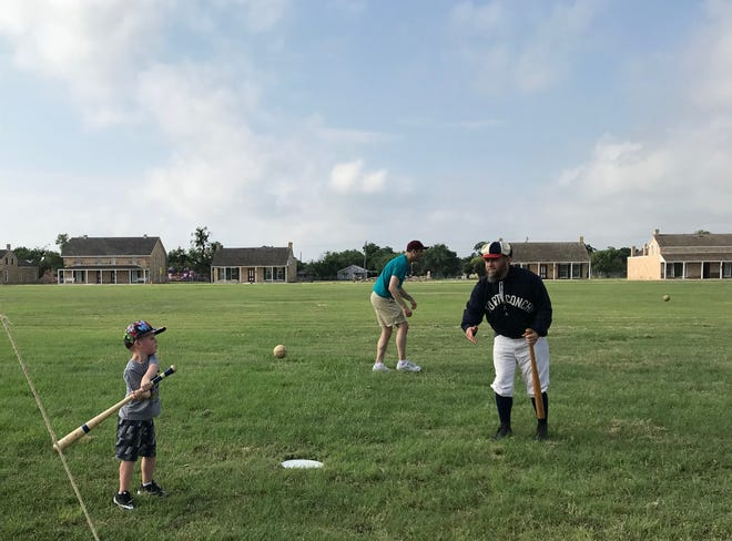 """Landon Robinson, 5, swings at a pitch from Cory """"Squirrel"""" Robinson during Fort Concho's  1800s baseball demonstration Saturday, June 1, at Fort Concho, 630 S. Oakes St."""