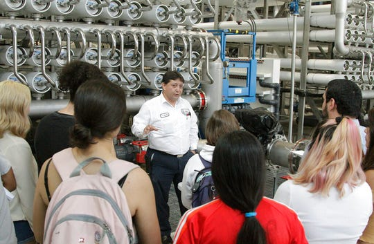 In this May 2, 2019, photo, college students listen as El Paso Water worker Hector Sepulveda explains the desalination process at a plant in El Paso, Texas. The silver pipes push water through tightly packed membranes inside the white pipes, drawing minerals out of the brine. As the planet warms and weather patterns turn more extreme, droughts - as well as floods - in the state generally have worsened. El Paso, which has about 700,000 people living in a desert region that gets only 9 inches (23 centimeters) of rain annually, receives international groups wanting to learn more about innovative facilities like the largest inland desalination plant in the United States.