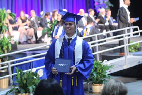A Lake View graduate holds up his diploma for a picture at the Foster Communications Coliseum, 50 E. 43rd St., Saturday, June 1, 2019.
