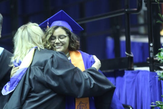A Central graduate hugs a staff member after receiving her diploma at the Junell Center, 2235 S. Jackson St., Saturday, June 1, 2019.
