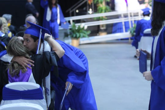 A Lake View graduate hugs a staff member after receiving his diploma at the Foster Communications Coliseum, 50 E. 43rd St., Saturday, June 1, 2019.