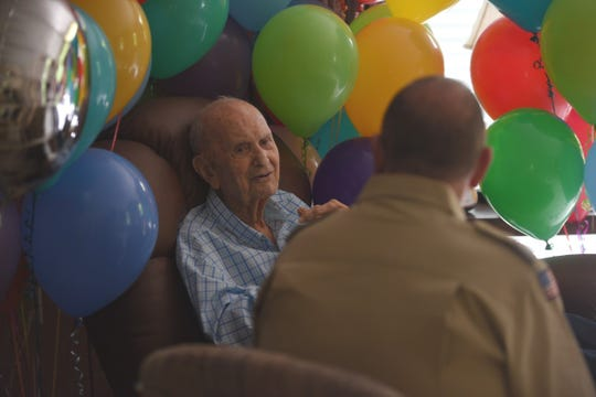 Duane Greenfield (left) sits surrounded by balloons during the celebration of his 101st birthday in Sioux Falls, South Dakota. Greenfield was awarded four Eagle Palms 84 years after he earned his Eagle Scout rank in Boy Scouts.