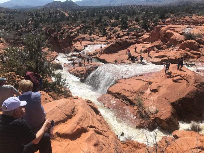 Crowds gather around the waterfalls beneath Gunlock Reservoir in this photograph dated March 24, 2019. The waterfalls, a popular destination for visitors when water levels in the reservoir are high enough to spill over, was the site of a reported drowning on Friday.