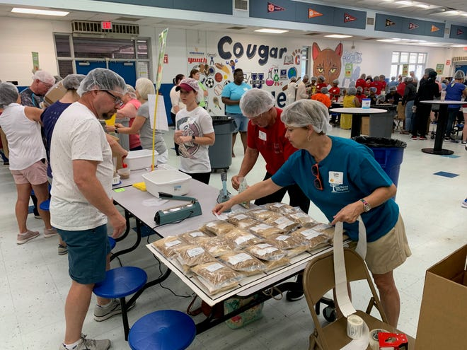 """Members of First Baptist church of Tallahassee labeling and packaging food Saturday at Godby High School as part of """"A Full Summer"""" to make sure kids don't go hungry while they are out of school."""