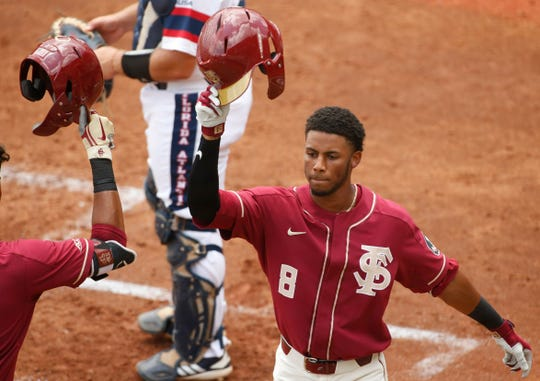 Florida State's J.C. Flowers (8) celebrates after scoring a run off a home run against Florida Atlantic at the NCAA college baseball regional tournament in Athens, Ga., Friday, May 31, 2019. (Joshua L. Jones/Athens Banner-Herald via AP)