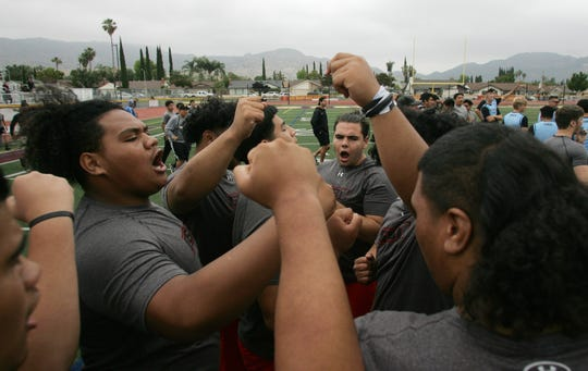 Jay Toia, left, and other members of the Grace Brethren team get pumped up before their tug-of-war battle with Royal at the annual Ventura County Football Coaches Hogs Tournament at Simi Valley High on Saturday.
