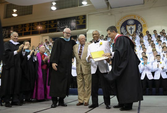Fred Smith (in tuxedo) poses with (from left) Salesianum School principal Rev. Christian Beretta, classmate James Owens and school president Brendan Kennealey during Salesianum's commencement Friday in Wilmington. Smith had been among the first black students to attend the school but never completed his degree when he was drafted at age 18. The school awarded him his diploma at the ceremony.