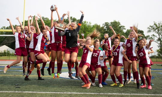 Caravel poses for photographers with a team leap and the title trophy after winning the DIAA Division II Girls Soccer Tournament championship game Saturday in Dover.