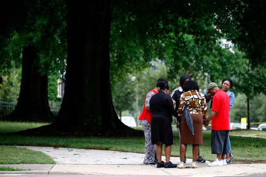 Members of Mount Olive Baptist Church pray near a municipal building that was the scene of a shooting on June 1, 2019, in Virginia Beach, Va. A longtime city employee opened fire at the building Friday before police shot and killed him, authorities said.