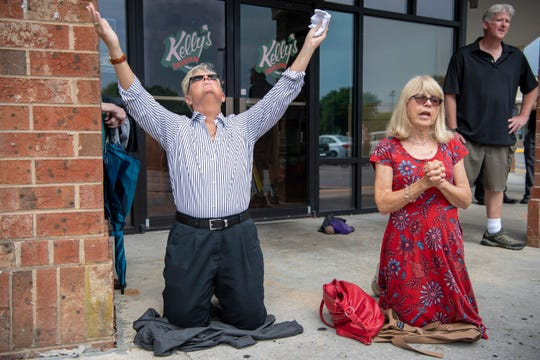 Cathy Whitley, left, of Virginia Beach and Brenda Flowers of Brentwood, TN, kneel in prayer at a vigil outside the Regal Cinemas in the Strawbridge neighborhood of Virginia Beach, Va. on June 1, 2019.