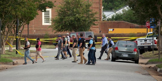 Police work the scene where eleven people were killed during a mass shooting at the Virginia Beach city public works building, Friday, May 31, 2019 in Virginia Beach, Va. A longtime, disgruntled city employee opened fire at a municipal building in Virginia Beach on Friday, killing 11 people before police fatally shot him, authorities said.  Six other people were wounded in the shooting, including a police officer whose bulletproof vest saved his life, said Virginia Beach Police Chief James Cervera. (L. Todd Spencer/The Virginian-Pilot via AP) ORG XMIT: VANOV108