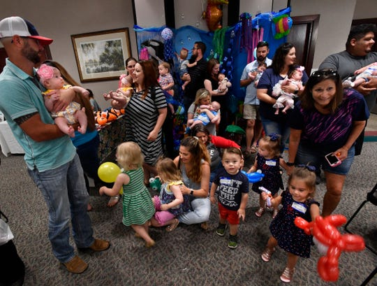 "Parents and children stand and move around after posing for a group portrait during the NICU Reunion on Saturday. Cookies, cakes and games were on hand for ""graduates"" of the Hendrick Health System's Neonatal Intensive Care Unit."