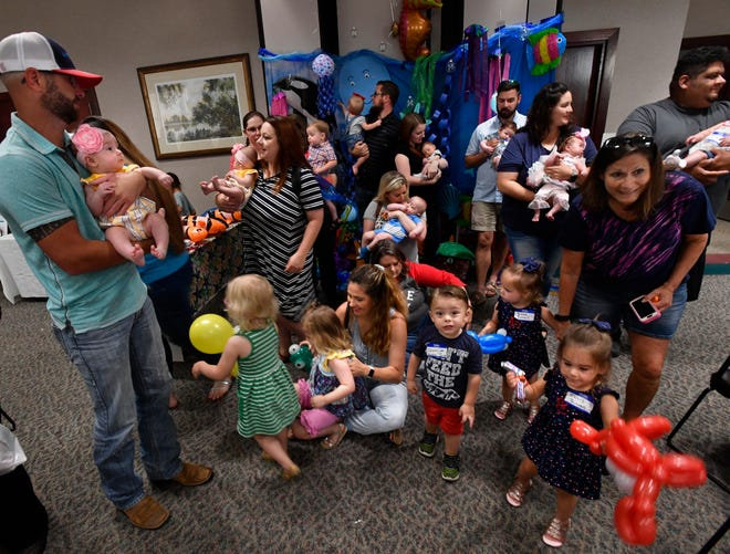 """Parents and children stand and move around after posing for a group portrait during the NICU Reunion on Saturday. Cookies, cakes and games were on hand for """"graduates"""" of the Hendrick Health System's Neonatal Intensive Care Unit."""