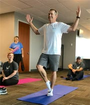 Health Carousel's CEO, Bill DeVille, doing on-site yoga with employees.
