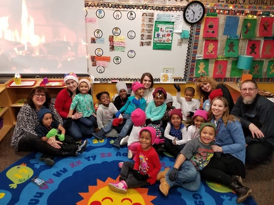Taft Law employees visiting a school and donating winter clothing