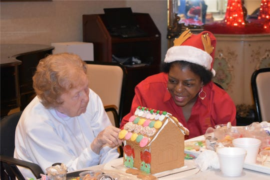 Maple Knoll employee with a resident making a gingerbread house.