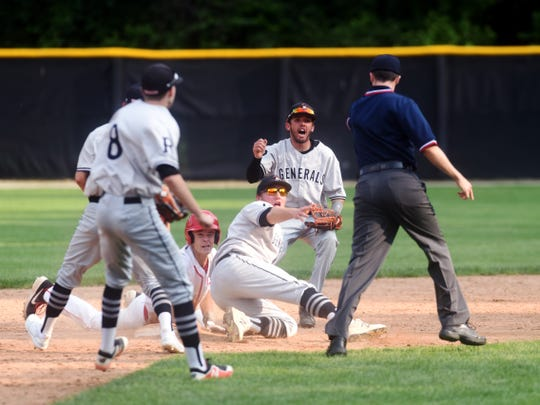 Center fielder Kaden Smith holds up the ball after tagging out Minford's Bailey Rowe during the seventh inning of Ridgewood's 4-3 win in a Division III regional final on Saturday at Ohio Dominican.