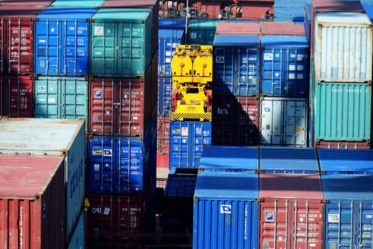 In this Thursday, May 23, 2019, photo, a crane lifts a shipping container at a port in Qingdao in eastern China's Shandong province.