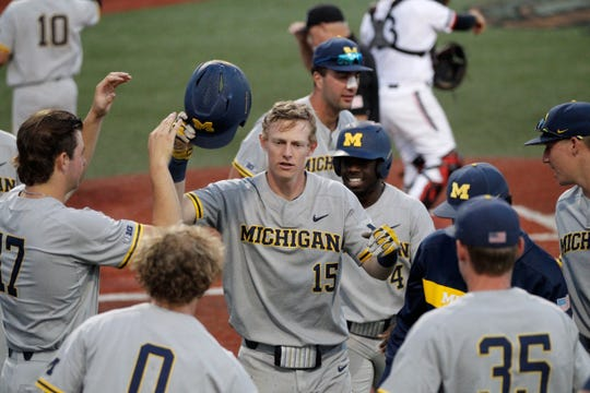 Jimmy Kerr celebrates with his Michigan teammates during Saturday's NCAA victory over Cincinnati.