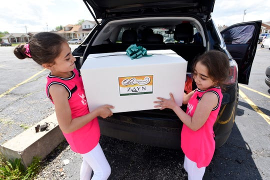 Volunteer sisters Aya Salmassi, 9, left, and Maya Salmassi, 7, put boxes filled with toys into their mother's car, which they distributed to needy area children.