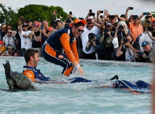 Car 9 driver Scott Dixon, top, of Chip Ganassi Racing gets cooled off and is joined by crew members in the James Scott Memorial Fountain after winning the Dual II IndyCar Series Race at the Chevrolet Detroit Belle Isle Grand Prix on Belle Isle in Detroit on June 2, 2019.