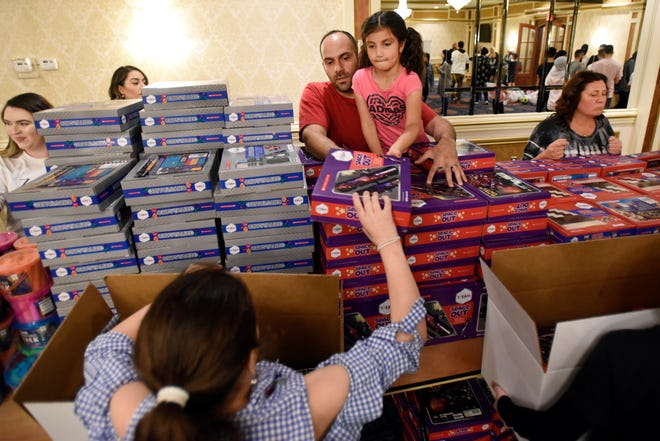Volunteer Maya Elkadri, 6, with help from her dad Kamel Elkadri, hands an educational toy to Nadine Bezzi, 10, who was filling a box to give to needy children.