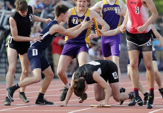 Runners collide at the final handoff of the 1,600-meter relay Saturday in La Crosse.