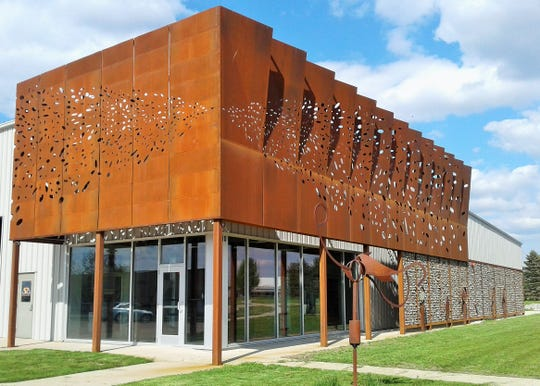 A façade of rusted steel artwork and a gabion rock wall wraps around the front of the Architectural Metal Folding building at the I-380 Industrial Park in North Liberty.